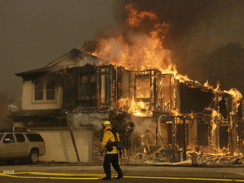 A firefighters walks near a home in Santa Rosa, Calif., Monday, Oct. 9, 2017. Wildfires whipped by powerful winds swept through Northern California sending residents on a headlong flight to safety through smoke and flames as homes burned. (AP Photo/Jeff Chiu)